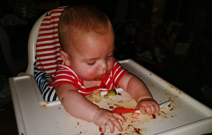 A baby eating broccoli baby lead weaning