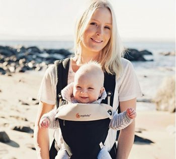 Happy mum on beach with baby in Ergobaby 360 bundle of joy
