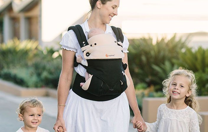 Mum walking with two children and baby in ergobaby 360 baby carrier